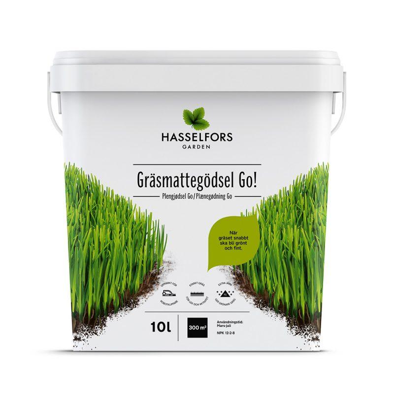 Vit låda med gödsel i och grönt gräs på