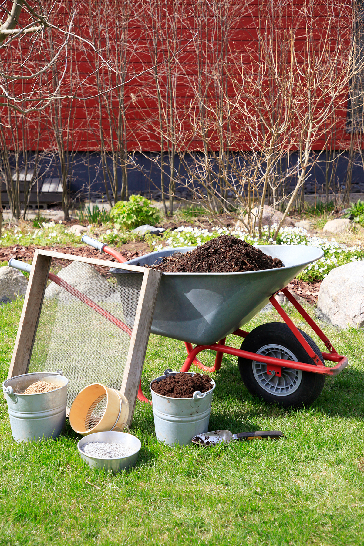 Skottkärra med torv samt hinkar med kompostblandning, torv, kalk och sand för en egen jordblandning